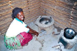 Stolze Besitzerin einer energie-effizienten Hersstelle. Diese wurde bei einer Fortbildung im Dorf Kighengi in Uganda erstellt. Sie spart Holz, die Zeit der Beschaffung und reduziert die Rauchbelastung.